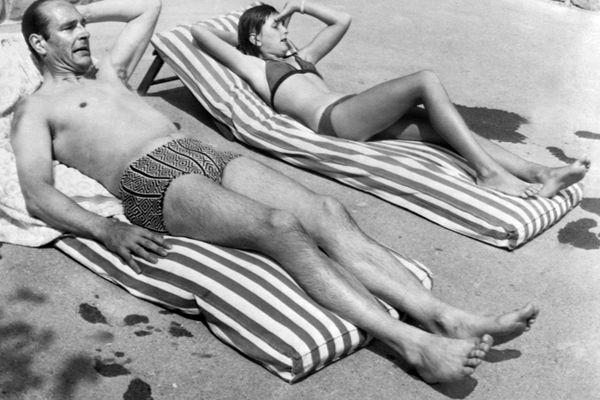Le Premier ministre Jacques Chirac et sa fille Claude, 11 ans, bronzent le 19 août 1974 au bord de la piscine de leur hôtel à Auron dans les Alpes-Maritimes.