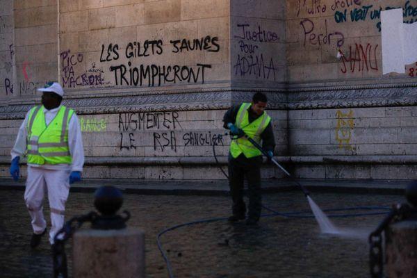 """""""Augmenter le RSA Sanglier"""" avait été tagué sur l'Arc de Triomphe lors de la troisième manifestation parisienne des gilets jaunes. Sur cette photo, des agents nettoient le site."""