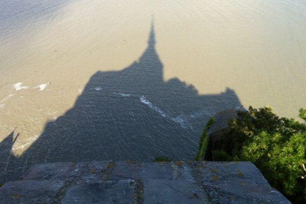 l'ombre du mont se reflète dans l'eau au pied des remparts