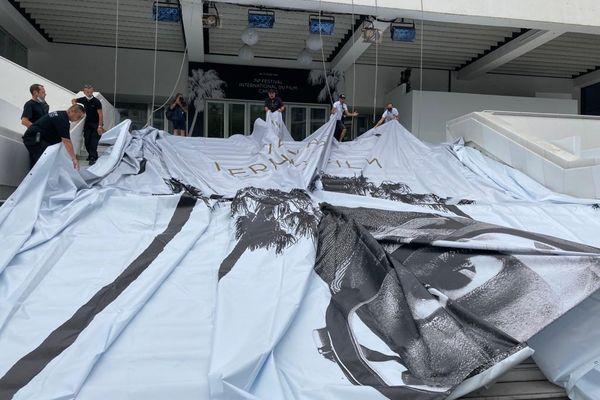 Plus d'une dizaine de personnes s'attèlent à monter l'affiche sur le Palais des Festivals de Cannes.