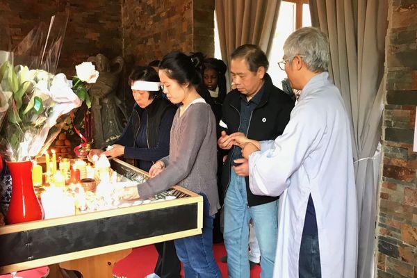 Nadine, une cousine de Sophie Le Tan, dépose une bougie sur l'autel.