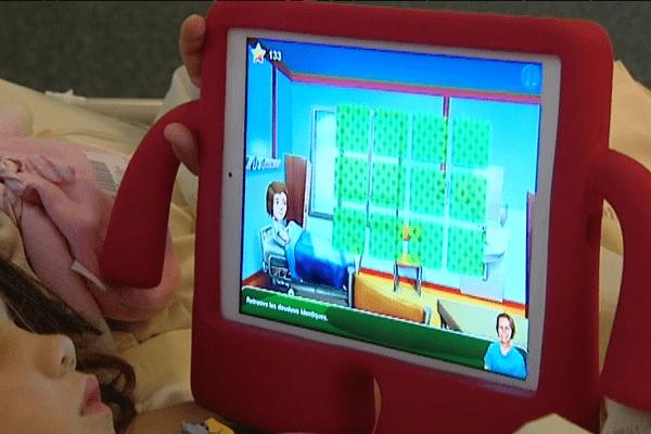 Après son intervention, Loanne se réveille doucement et utilise sa tablette interactive.