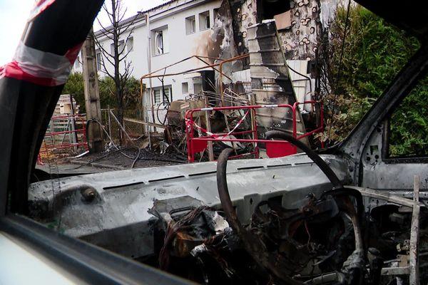 Evreux le 14 juillet 2020 : une des voitures brûlées avec à l'arrière-plan l'habitation incendiée dans le quartier de Nétreville.