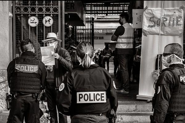 Contrôle des attestations de déplacement à la sortie du marché des halles par la police municipale.