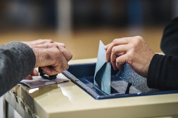 Un électeur glisse son bulletin dans l'urne - Photo d'illustration