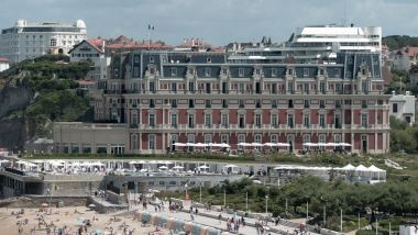 """L'Hotel du Palais accueillera le G7 à Biarritz, du 24 au 26 août 2019. La cité balnéaire sera sous très haute surveillance pendant le sommet international. People swim in the sea and walk on the beach in front of the """"Hotel du Palais"""" in Biarritz, on August 13, 2019. The French southwestern seaside resort of Biarritz, known in France as the 'Cote Basque', will host the 45th Group of Seven (G7) nations annual summit from August 24-26, 2019. / © IROZ GAIZKA / AFP"""