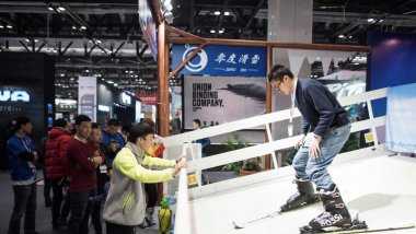 "Un homme sur un simulateur de ski à l"" International Trade Show for Mountain and Winter Technologies"" à Pékin, le 15 février 2017. / © FRED DUFOUR / AFP"